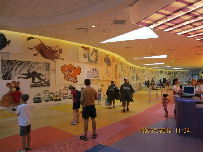 "The other side of the check-in area. All the way on the right are black and white ""rough"" sketches. As you go along the wall they become more finished and colored in. VERY cool concept."