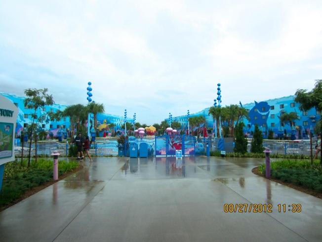 This is the Finding Nemo section viewed from just outside the main lobby. This is all the further we made it outside because of the rain and my pride (explaining in a bit). The pool is straight ahead and buildings flank either side of it. VERY colorful and VERY fun looking!