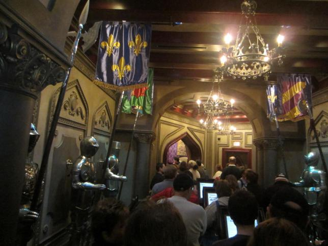 The corridor leading to the ordering room. The doorway at the end leads to the ordering room. The knights on each side of the rooms talk and have conversations with each other. There are electronic menus posted on a couple pedestal screens in the middle.